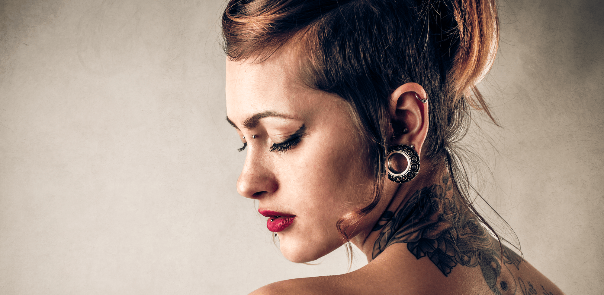 Tattoed girl with ear and facial piercings