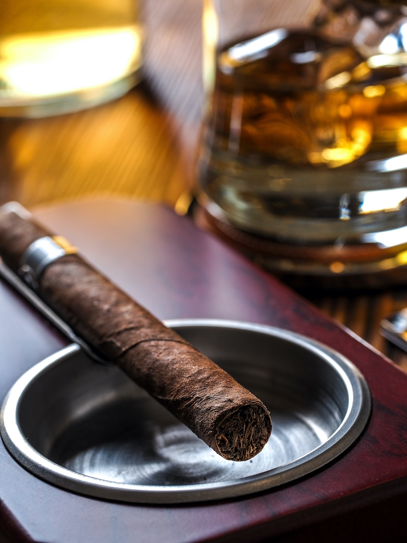 Cigar on an ashtray with whiskey in the back